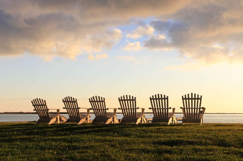 Six Adirondack chairs sitting by the Sea